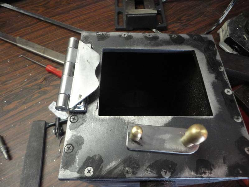 The hinge is a plain old door hinge, cut and shaped. I shimmed it so that  it would make the door fit nicely with the gasket thickness taken into  account. - Duckworks - Homemade Wood Stove For A Small Boat
